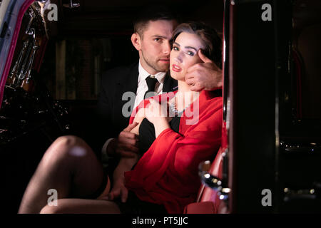 Good looking sexy couple, handsome man in suit, beatiful woman in red dress, touching, holding each other passionately in vintage car - Stock Image