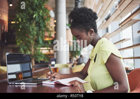 Beautiful African American working on a laptop in a restaurant. A thoughtful beautiful woman, all in the job. - Stock Image