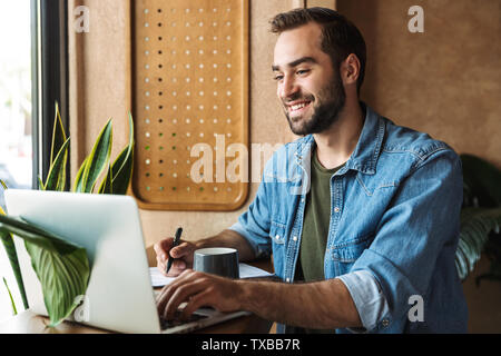 Photo of smiling bearded man wearing denim shirt writing and typing on laptop while working in cafe indoors - Stock Image