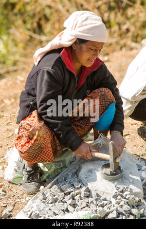 Local woman crouching and crushing stones with hammer, Nepal - Stock Image