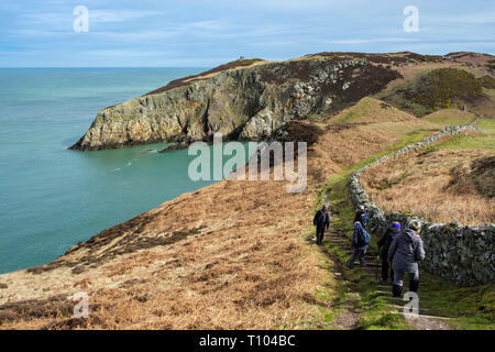 Walkers hiking on the coast path approaching Porth Llanlleiana from Cemaes, Isle of Anglesey, Wales, UK, Britain - Stock Image