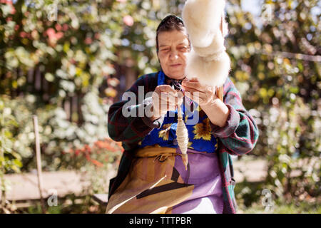 Senior woman winding thread on spindle while sitting at yard - Stock Image