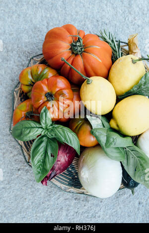 Vegetables and herbs in basket - Stock Image