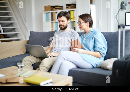Young spouses sitting on sofa and looking through online hot tour offers while choosing suitable one - Stock Image