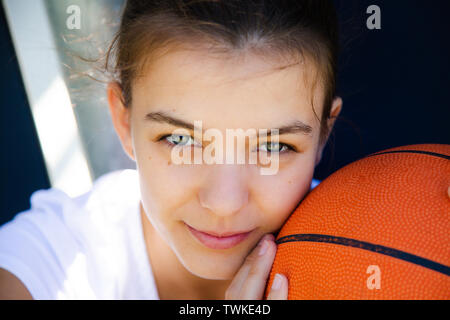 Portrait of a beautiful and young female basketball player with face resting on the ball - Stock Image