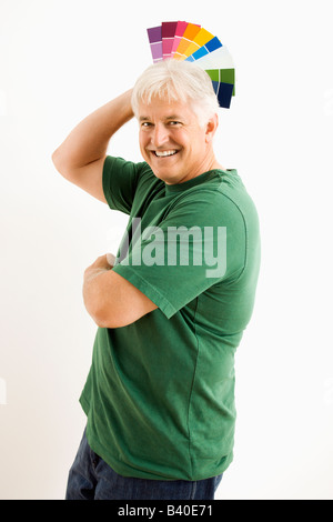 Middle aged man fanning paint swatches over his head - Stock Image