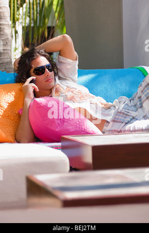 Young man lying on a couch and talking on the mobile phone - Stock Image