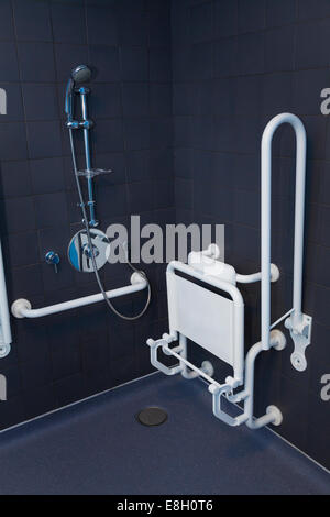 Disabled shower in wet room with hand rails and seat in up position. - Stock Image