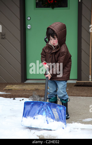 Young boy shoveling snow - Stock Image
