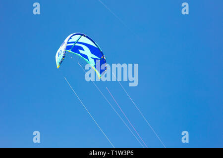 Detail of kite flying in blue sky background. This kite is used to play kitesurfing. - Stock Image