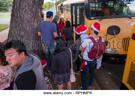 Group of people with some wearing a Santa hat stocking caps loading onto chartered school buses parked on roadside, Kahala, Honolulu, Oahu, Hawaii, US - Stock Image