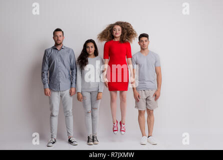 A portrait of young group of friends standing in a studio, one is jumping. - Stock Image