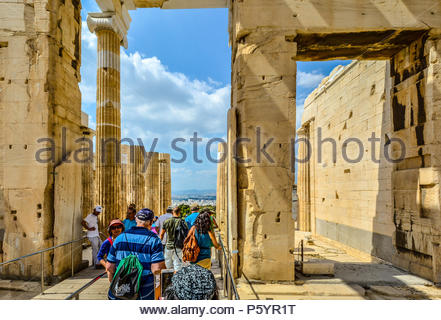 Tourists pass through the ancient ruins on Acropolis Hill in Athens, Greece with modern city of Athens spread out in front of them. - Stock Image