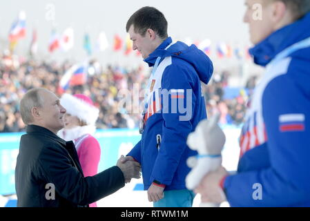 Krasnoyarsk, Russia. 03rd Mar, 2019. KRASNOYARSK, RUSSIA - MARCH 3, 2019: Russia's President Vladimir Putin (L) and silver medallist Anton Timashov of Russia at a victory ceremony for the men's 10km cross-country skiing race during the 2019 Winter Universiade. Alexei Druzhinin/Russian Presidential Press and Information Office/TASS Credit: ITAR-TASS News Agency/Alamy Live News - Stock Image