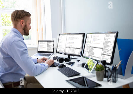 Computer programmer writing program code on computer in office - Stock Image
