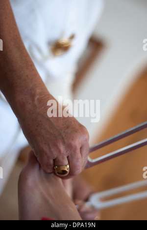 Close up of therapist giving healing tuning fork treatment to young woman. - Stock Image