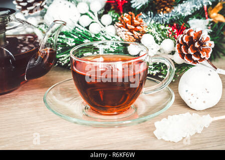 Christmas holiday background with hot cup of black tea, crystal sugar on a stick and Christmas decorations - Stock Image