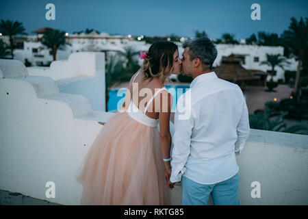 Happy newlyweds kiss on roof of house against background of blue sky during the honeymoon in Egypt in the evening. - Stock Image