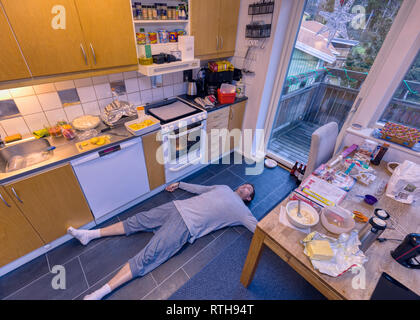 Collapsed or flat out exhausted adult caucasian man laying on the kitchen floor surrounded by cooking and baking in progress - Stock Image