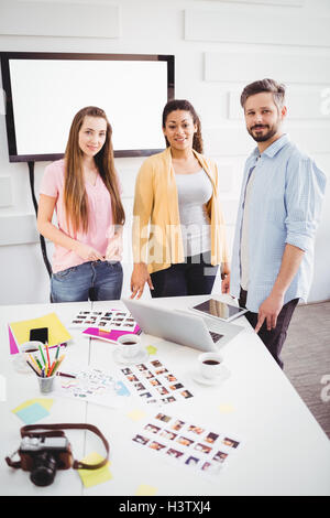 Portrait of confident editors standing in meeting room at creative office - Stock Image