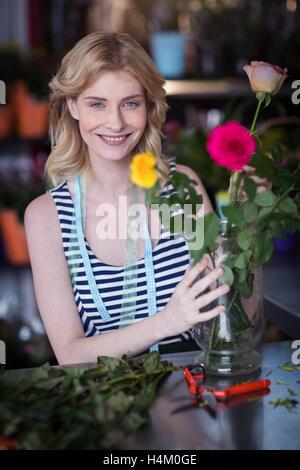 Smiling female florist arranging flower bouquet in vase at flower shop - Stock Image