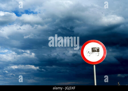 Heavy lorry road sign showing industrial limitations set against a stormy blue overcast sky - Stock Image