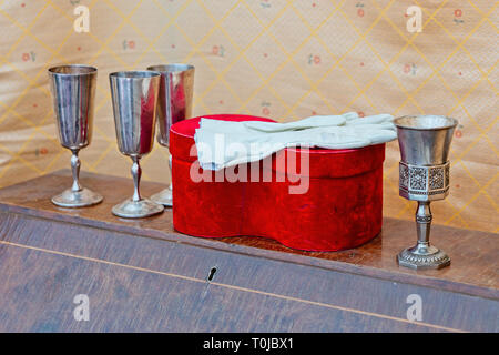 Still-life with white gloves on the red gift box, four metal wine glasses on a vintage wooden piece of furniture - Stock Image