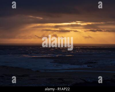 Sun rays breaking the cloud and reflecting in the water over Iceland - Stock Image