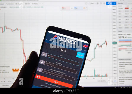 MONTREAL, CANADA - APRIL 26, 2019: Bitmex cryptocurrency exchange logo and application on Android Samsung Galaxy s9 Plus screen in a hand over a lapto - Stock Image