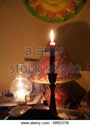 Kerosene lamp and a candle are lighting a room during a power outage in Jinnotega, Nicaragua - Stock Image