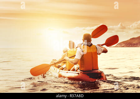 Family with son is walking by kayak or canoe at sunset sea bay. Kayaking or canoeing concept - Stock Image