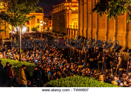 The procession of the Brotherhood (Hermandad) El Calvario winds around the Seville Cathedral predawn on Good Friday, Holy Week (Semana Santa), Seville - Stock Image