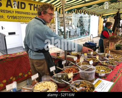 Man selling olives on a street market stall, Sherborne, Dorset, England - Stock Image