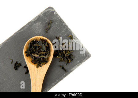 Small pieces of dried Wakame (Undaria pinnatifida), edible seaweed, ingredient to different foods in wooden spoon on black stone cutting board isolate - Stock Image