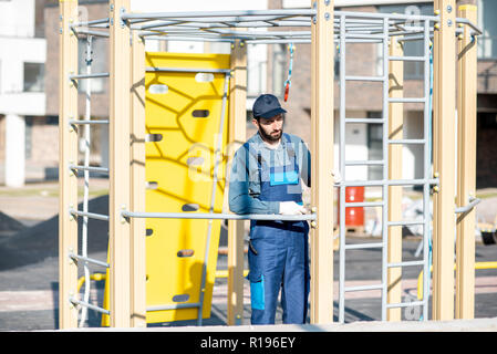 Handsome workman in uniform mounting ladder for kids playing on the playground outdoors - Stock Image