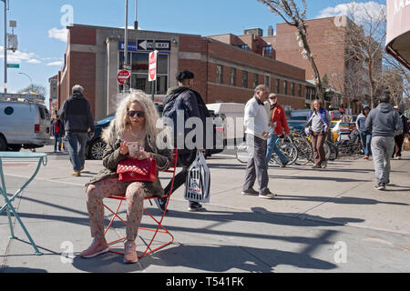 A street scene featuring a seated woman with long blond hair texting on her cell phone. In Jackson Heights, Queens, New York City. - Stock Image