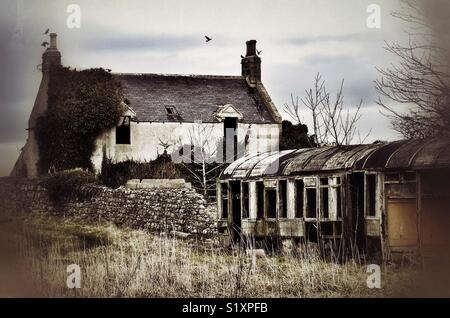 Derelict house with disused, derelict train carriage in the garden. - Stock Image