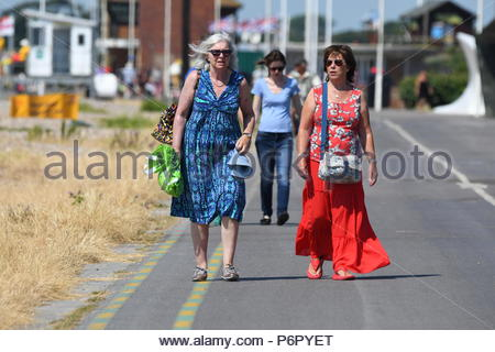 Littlehampton, UK. Monday 2nd July 2018. People walking on the seafront promenade on another very warm and humid morning in Littlehampton, on the South Coast. Credit: Geoff Smith / Alamy Live News. - Stock Image