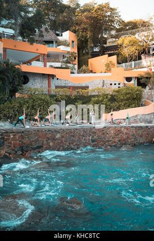 Group of multiple people exercising. Yoga retreat Puerto Vallarta - Mismaloya, Mexico - Stock Image