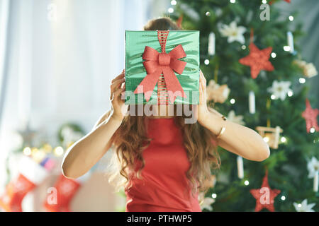 young woman in red dress near Christmas tree holding green Christmas present box in the front of face - Stock Image