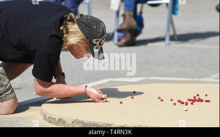 Crawley Sussex, UK. 19th Apr, 2019. Action in the hot sunny weather at the World Marbles Championship held at The Greyhound pub at Tinsley Green near Crawley in Sussex . The annual event has been held on Good Friday every year since the 1930s and is open to players from around the world Credit: Simon Dack/Alamy Live News - Stock Image