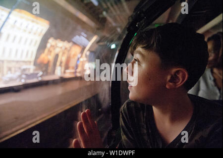 Teenager riding on the Mail Rail train at the postal museum, London, - Stock Image