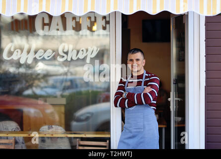A handsome young coffee shop owner standing in the entrance of his shop. Coffee shop inscription on the window of the store. He is a proud shop owner - Stock Image
