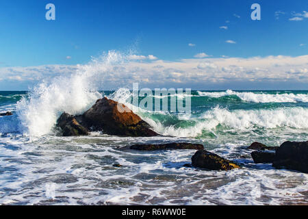storm at sea, splashing waves and rocks on the shore - Stock Image