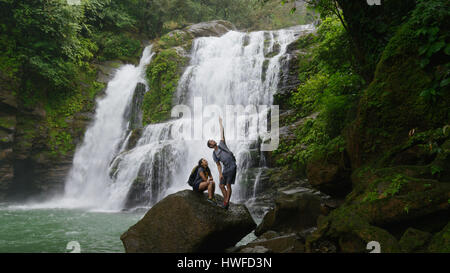 Low angle view of couple standing on boulder pointing and admiring scenic view near tropical waterfall - Stock Image