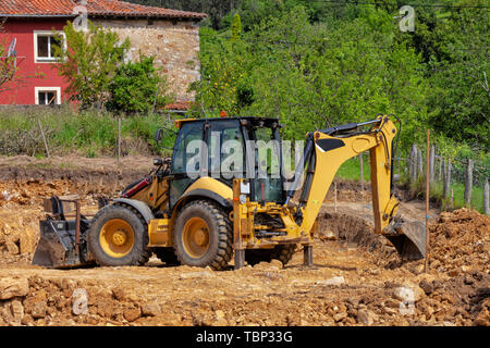 A backhoe excavating earth in a construction site. - Stock Image