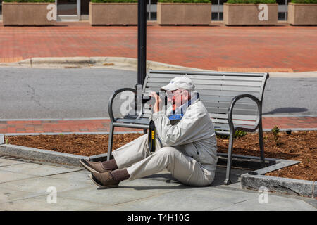 ASHEVILLE, NC, USA-4/11/19:  A senior man sitting on the ground in front of a bench taking pictures with Nikon camera, and smiling. - Stock Image