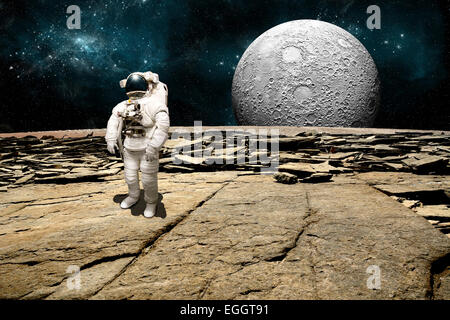 An astronaut surveys his situation after being marooned on a barren planet. A large, heavily crated moon rises over - Stock Image