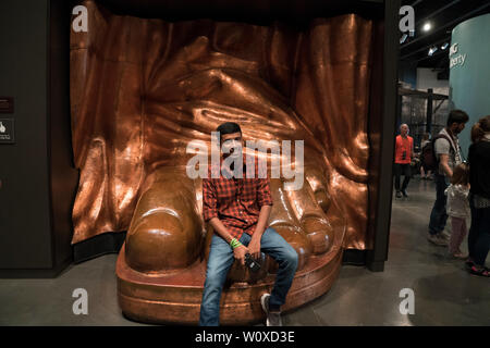A visitor to the Statue of Liberty Museum from India perched on a replica of the statue's foot to have his picture taken. - Stock Image