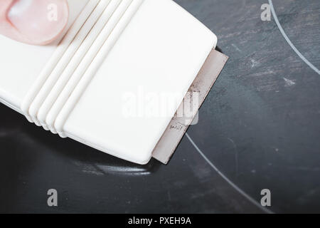 Cleaning A Ceramic Glass Cooktop With A Glass Scraper - Stock Image